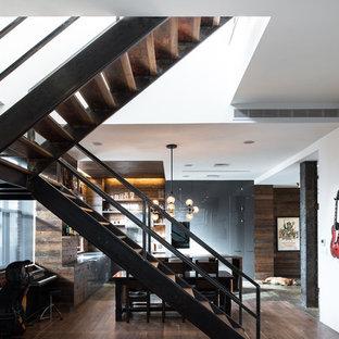 Foto de escalera en U, industrial, de tamaño medio, sin contrahuella, con escalones de madera y barandilla de metal