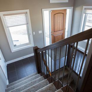 Foto de escalera de estilo americano, grande, con escalones enmoquetados, contrahuellas de hormigón y barandilla de varios materiales