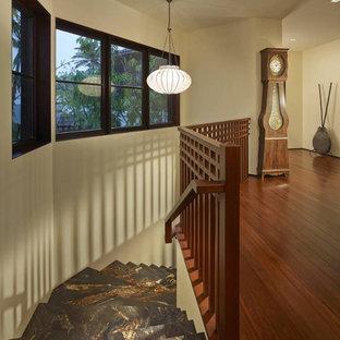 Modelo de escalera curva, de estilo zen, grande, con escalones de mármol, contrahuellas de madera y barandilla de madera