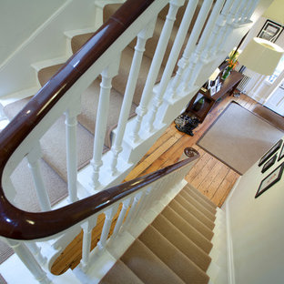 This is an example of a large victorian painted wood u-shaped staircase in London with painted wood risers.