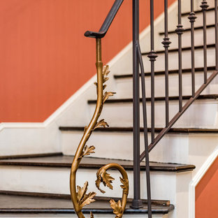Staircase - traditional wooden curved metal railing staircase idea in Raleigh with painted risers