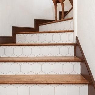 Imagen de escalera curva, mediterránea, grande, con escalones de madera y contrahuellas con baldosas y/o azulejos