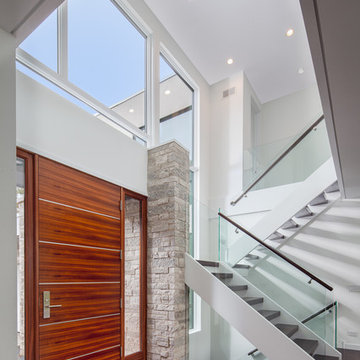 2-story foyer with glass and wood staircase and African mahogany front door