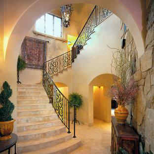 Ejemplo de escalera en U, mediterránea, con escalones de travertino, contrahuellas de travertino y barandilla de metal