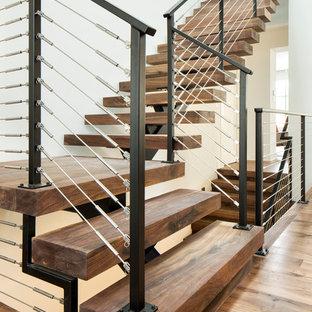 На фото: угловая лестница в современном стиле с деревянными ступенями и перилами из тросов без подступенок