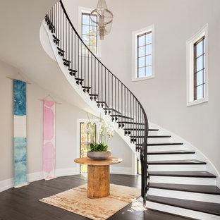 Diseño de escalera curva, tradicional renovada, con escalones de madera, contrahuellas de madera pintada y barandilla de metal