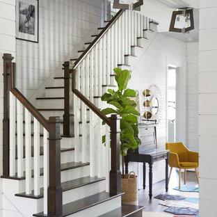 ヒューストンの大きい木のトラディショナルスタイルのおしゃれなかね折れ階段 (フローリングの蹴込み板、木材の手すり) の写真