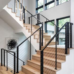 Выдающиеся фото от архитекторов и дизайнеров интерьера: большая п-образная лестница в современном стиле с деревянными ступенями, деревянными подступенками и перилами из тросов