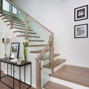 """Esempio di una scala a """"U"""" moderna di medie dimensioni con pedata in legno, alzata in vetro e parapetto in legno"""