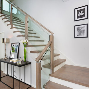 Inspiration for a mid-sized modern wooden u-shaped wood railing staircase remodel in Other with glass risers