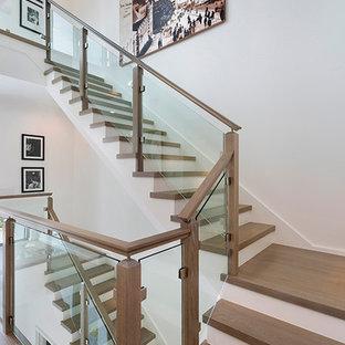 Bild på en mellanstor funkis u-trappa i trä, med sättsteg i glas och räcke i trä