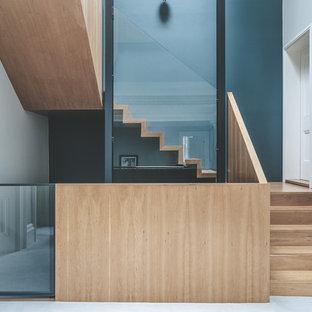 他の地域の木のコンテンポラリースタイルのおしゃれな折り返し階段 (木の蹴込み板、ガラスの手すり) の写真