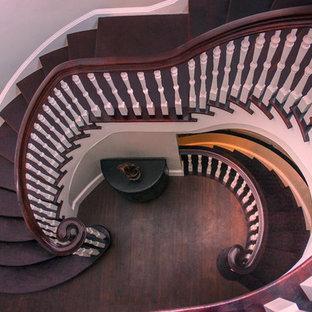 ワシントンD.C.の広い木のトランジショナルスタイルのおしゃれならせん階段 (木の蹴込み板、木材の手すり) の写真