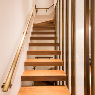 Trendy wooden l-shaped open and metal railing staircase photo in New York