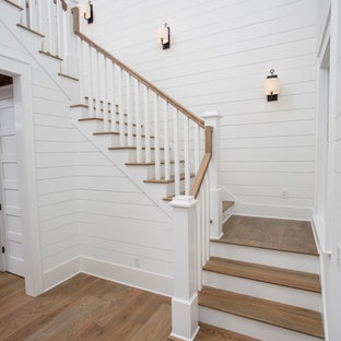 Inspiration for a large country wooden u-shaped wood railing staircase remodel in Jacksonville with wooden risers