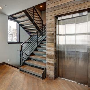 Exempel på en stor modern u-trappa i trä, med öppna sättsteg och räcke i metall