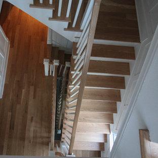 """Immagine di una grande scala a """"L"""" shabby-chic style con alzata in legno, pedata in legno e parapetto in legno"""
