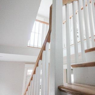 Exemple d'un grand escalier romantique en L avec des contremarches en bois, des marches en bois et un garde-corps en bois.