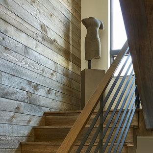 """Immagine di una grande scala a """"U"""" rustica con pedata in legno, alzata in legno e parapetto in legno"""