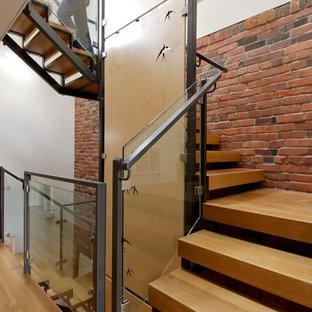 Imagen de escalera curva, moderna, de tamaño medio, sin contrahuella, con escalones de madera y barandilla de metal