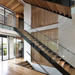 Diseño de escalera recta, actual, sin contrahuella, con escalones de madera y barandilla de vidrio