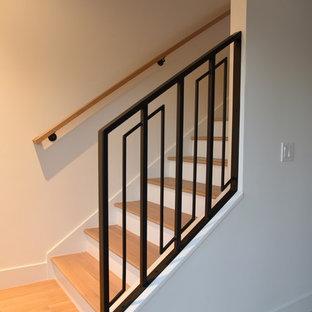 Diseño de escalera recta, moderna, de tamaño medio, con escalones de madera, contrahuellas de madera pintada y barandilla de madera