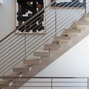 Esempio di una scala sospesa contemporanea di medie dimensioni con pedata in legno, nessuna alzata e parapetto in metallo