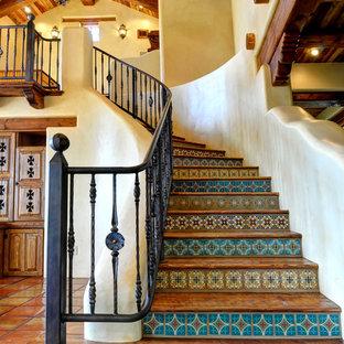 Modelo de escalera curva, de estilo americano, con escalones de madera y contrahuellas con baldosas y/o azulejos