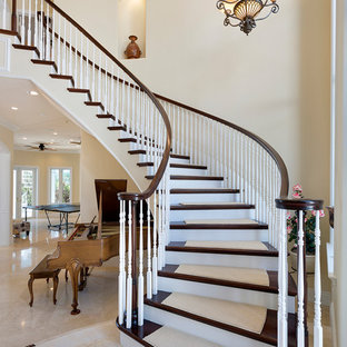 Huge transitional painted spiral wood railing staircase photo in Miami with wooden risers