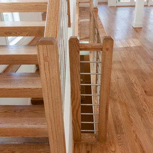 Esempio di una grande scala sospesa design con pedata in legno e parapetto in materiali misti