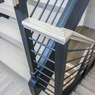 Foto de escalera suspendida, minimalista, grande, con escalones de madera y barandilla de metal