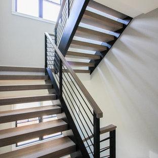 Ejemplo de escalera suspendida, minimalista, grande, con escalones de madera y barandilla de metal