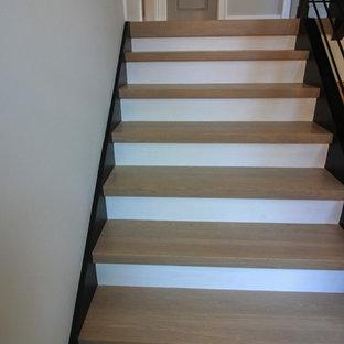 Imagen de escalera suspendida, moderna, grande, con escalones de madera y barandilla de metal