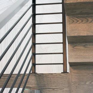 Foto de escalera suspendida, bohemia, grande, con escalones de madera, contrahuellas de madera y barandilla de metal