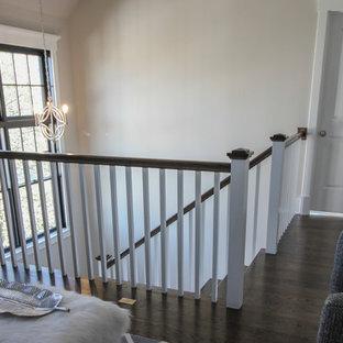 Imagen de escalera en U, minimalista, de tamaño medio, con escalones de travertino, contrahuellas de madera y barandilla de madera