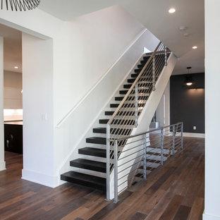 Ejemplo de escalera suspendida, contemporánea, grande, con escalones de madera y barandilla de metal