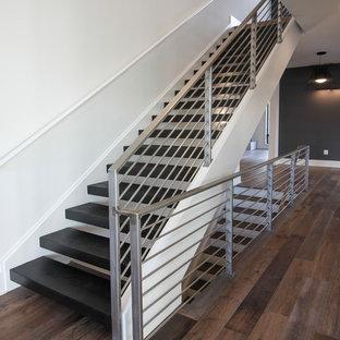 Foto de escalera suspendida, contemporánea, grande, con escalones de madera y barandilla de metal