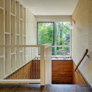На фото: большая п-образная лестница в стиле ретро с деревянными ступенями и крашенными деревянными подступенками с