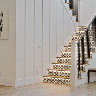 """Esempio di una grande scala a """"U"""" tradizionale con pedata in legno, alzata piastrellata e parapetto in metallo"""