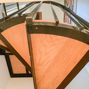 Ispirazione per una piccola scala a chiocciola minimal con pedata in legno e parapetto in metallo