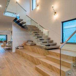 Foto på en funkis l-trappa i trä, med öppna sättsteg och räcke i glas