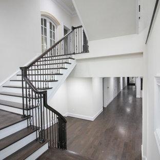 Ejemplo de escalera suspendida, tradicional renovada, grande, con escalones de madera, contrahuellas de madera y barandilla de vidrio
