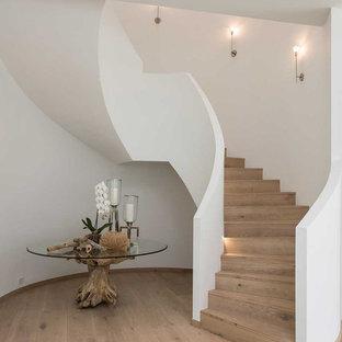 Modelo de escalera curva, actual, con escalones de madera y contrahuellas de madera