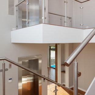 """Foto di una grande scala a """"U"""" minimalista con pedata in legno, alzata in legno, parapetto in vetro e pareti in mattoni"""