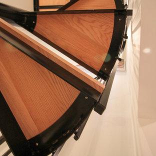 Foto di una grande scala a chiocciola minimal con pedata in legno, alzata in legno e parapetto in materiali misti
