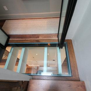 Foto di un'ampia scala sospesa minimal con pedata in vetro, nessuna alzata e parapetto in vetro