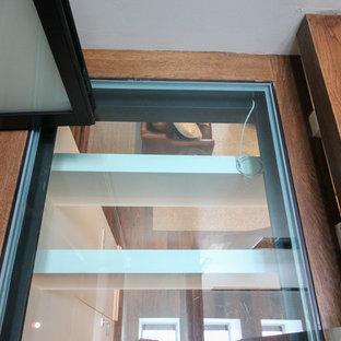 Esempio di un'ampia scala sospesa design con pedata in vetro, nessuna alzata e parapetto in vetro