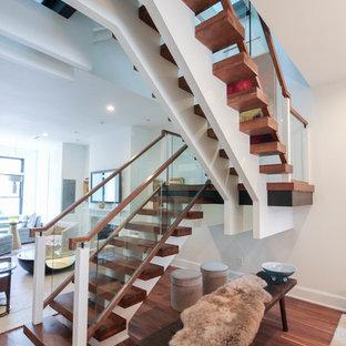 На фото: огромная лестница на больцах в современном стиле с стеклянными ступенями и стеклянными перилами без подступенок