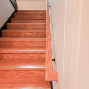 Inspiration pour un grand escalier design en U avec des marches en bois et un garde-corps en matériaux mixtes.