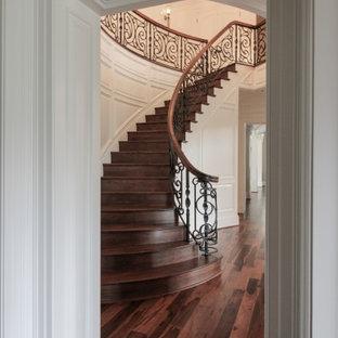 Immagine di una grande scala curva eclettica con pedata in legno, alzata in legno e parapetto in materiali misti